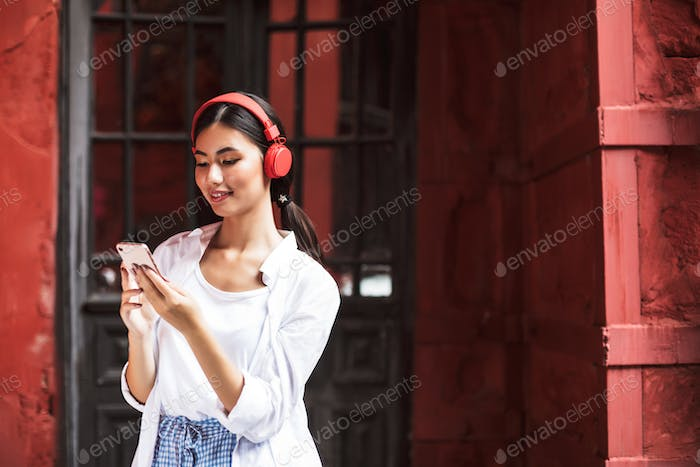 Beautiful smiling girl in white shirt and red headphones happily