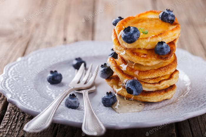 Pancake folded stack of with liquid honey and fresh blueberries