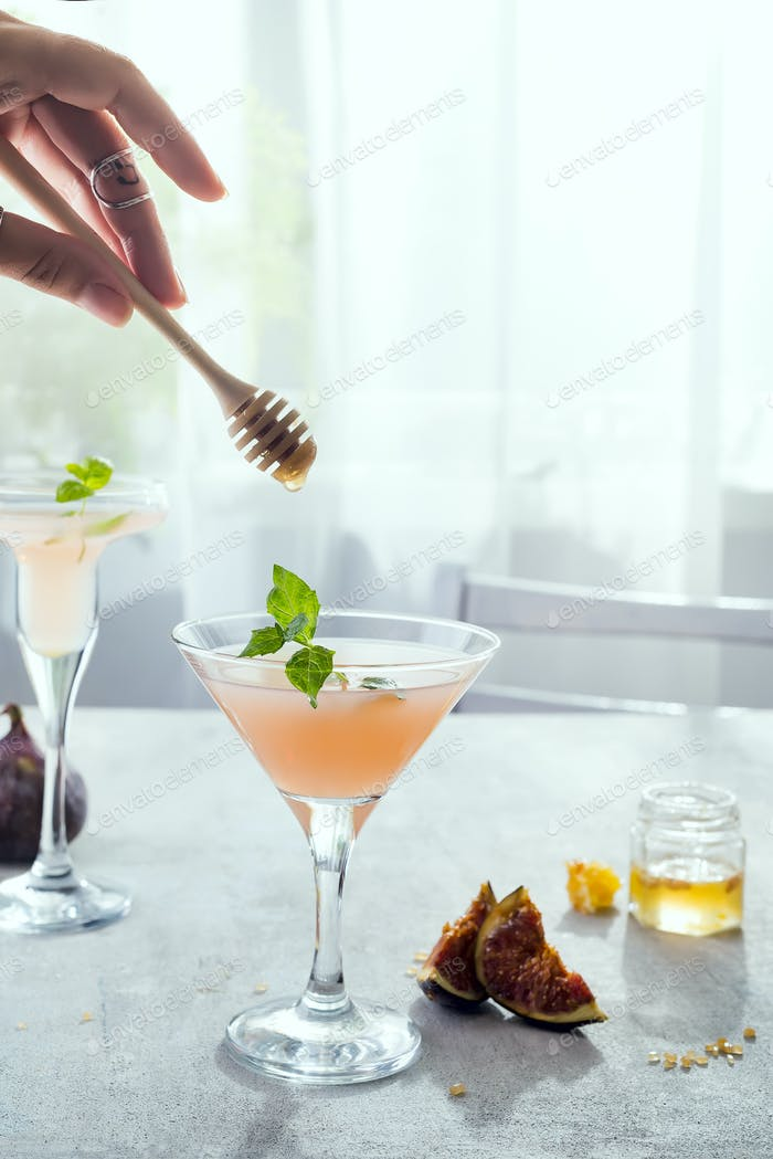 girl holds a stick for honey over rose exotic cocktail and figs, honey on stone background