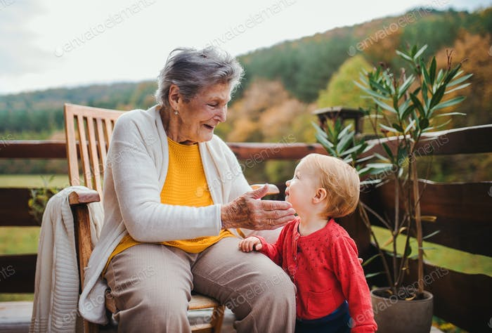 Elderly woman sitting with a toddler great-grandchild on a terrace in autumn.