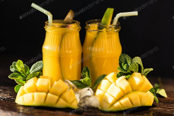 Mango juice and mango on wood table