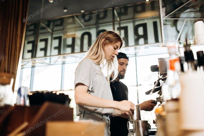 Dos jóvenes baristas, una rubia y un Hombre elegante con barba, se muestran cocinando café juntos en un