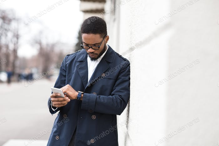 Handsome black manager checking time on his wristwatch