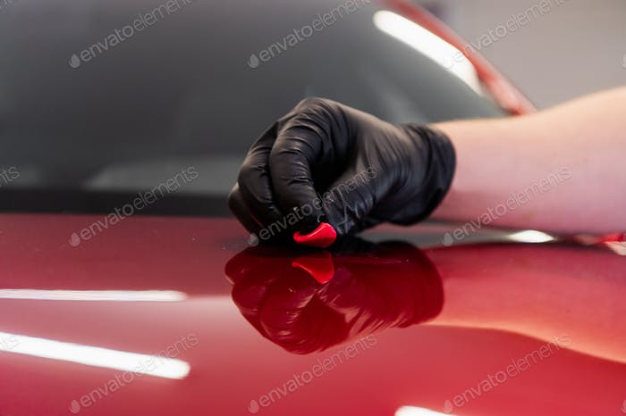 The master removes small dirt pieces from the car bonnet surface with special clay before polishing
