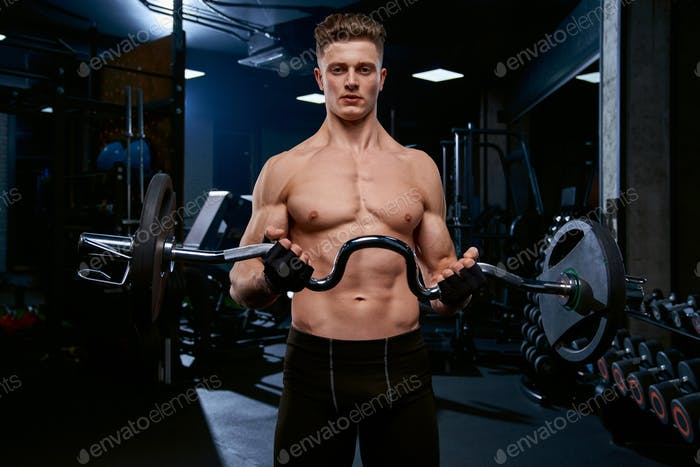 Shirtless sportsman training biceps with barbell