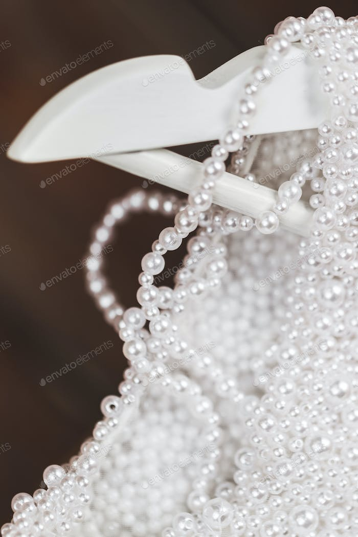 Details of shining wedding dress with pearls and gemstones closeup