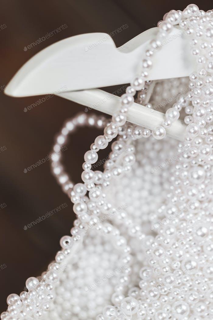 Details des glänzenden Brautkleides mit Perlen und Edelsteinen Nahaufnahme