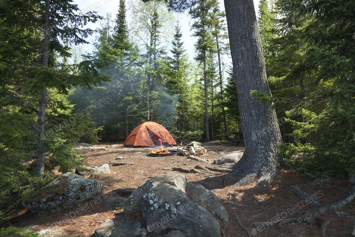 Campsite with orange tent and fire set among pines in the northern Minnesota wilderness