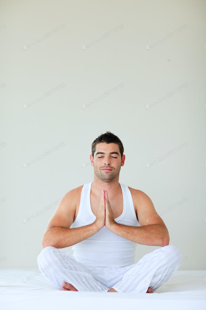 Young man doing yoga in bed with clossed eyes