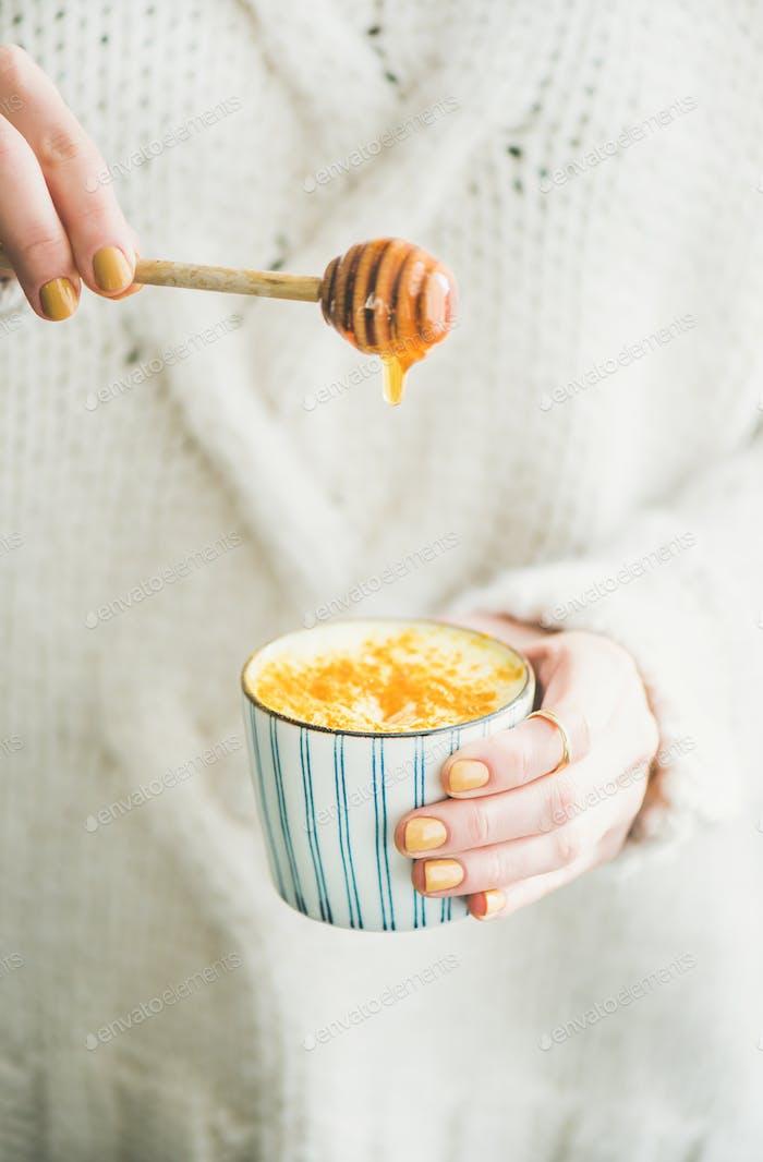 Turmeric latte or golden milk with honey in woman's hands