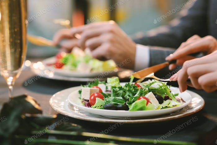 Closeup Of Unrecognizable Couple Eating Greek Salad At Dinner In Restaurant