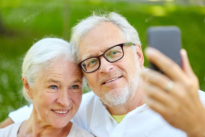 senior couple with smartphone taking selfie in summer