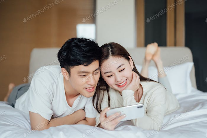 Young couple watching videos with smartphone in bedroom