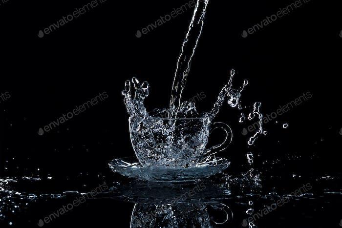 Wasser strömt in die Tasse auf einem schwarzen Hintergrund, Studiolicht