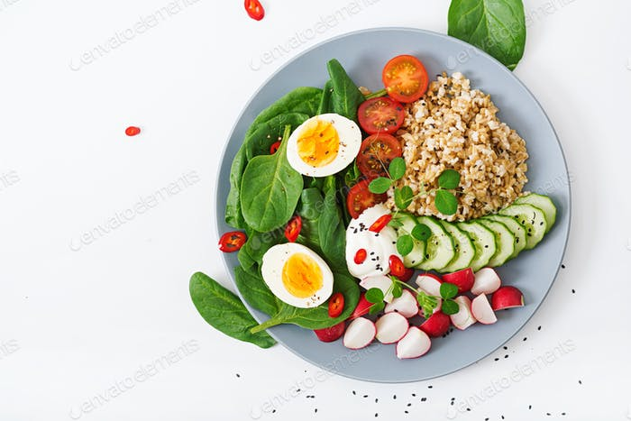 Healthy salad of fresh vegetables - tomatoes, cucumber, radish, egg, spinach and oatmeal