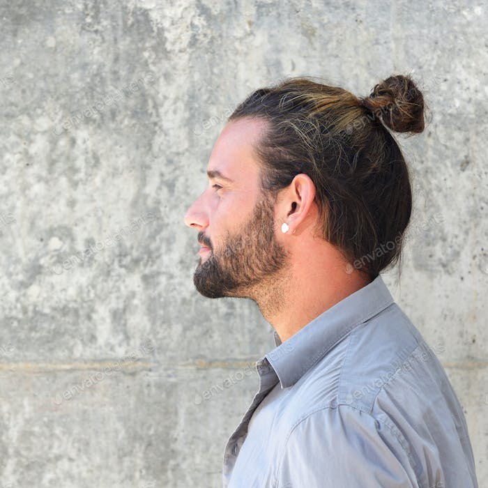 Side portrait of serious man with beard and hair bun
