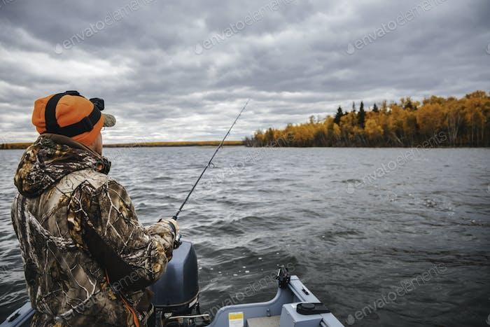 Ein Mann, der am See angelt. Angeln von einem Boot Herbstsaison.