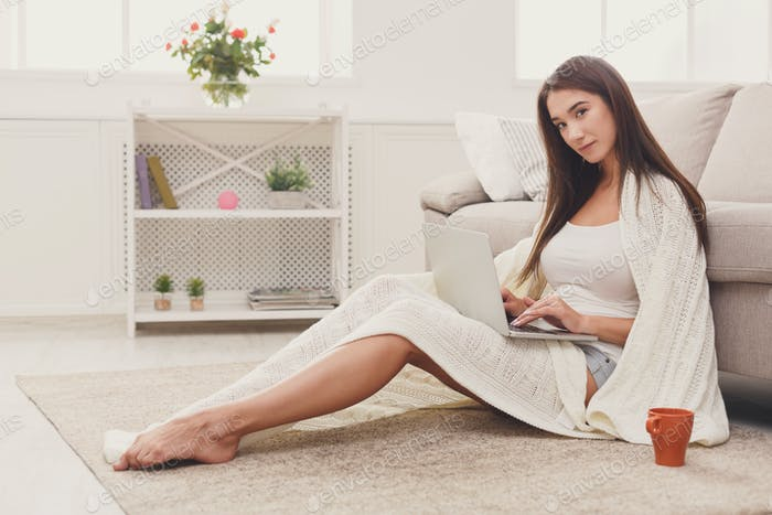 Cozy home. Girl in blanket with laptop