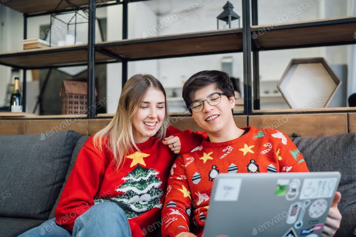 Happy couple with laptop together on sofa, smiling young girl and guy having fun talking at home
