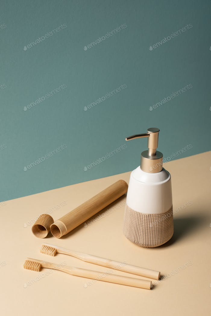 Toothbrushes, toothbrush case, liquid soap dispenser on beige and grey, zero waste concept