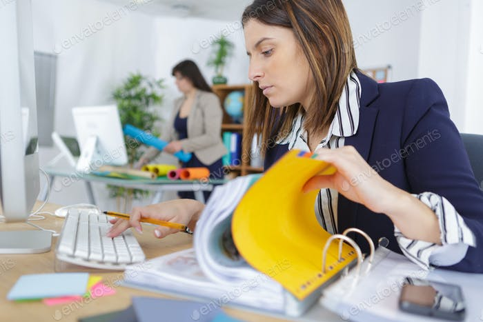 young businesswoman looking through a stack of file folders