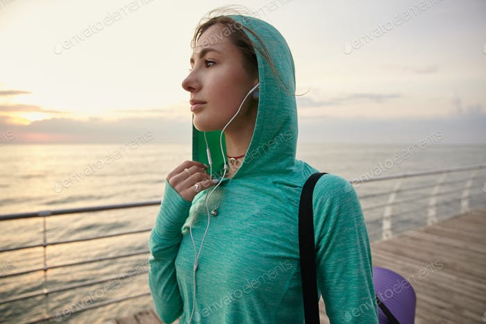 Portrait of young woman walking at the seaside, going to practicing yoga
