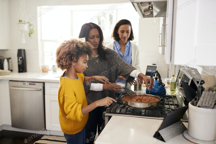 Pre-teen black girl standing at the hob in the kitchen preparing food with her grandmother