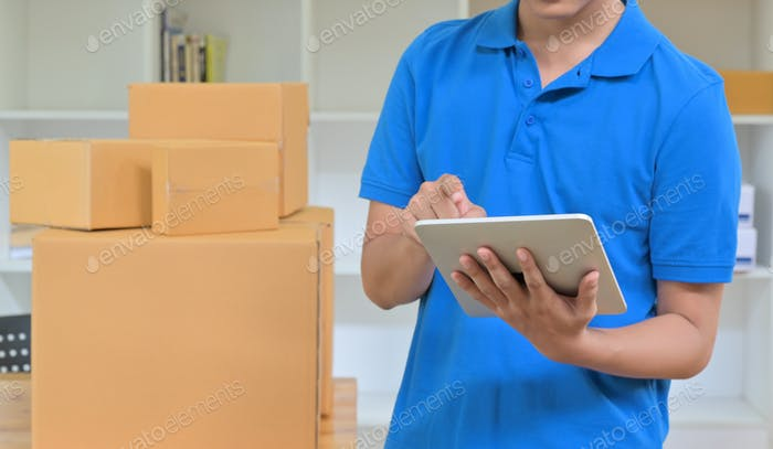Der Kurier verwendet ein Tablet, um die Lieferinformationen aufzuzeichnen.
