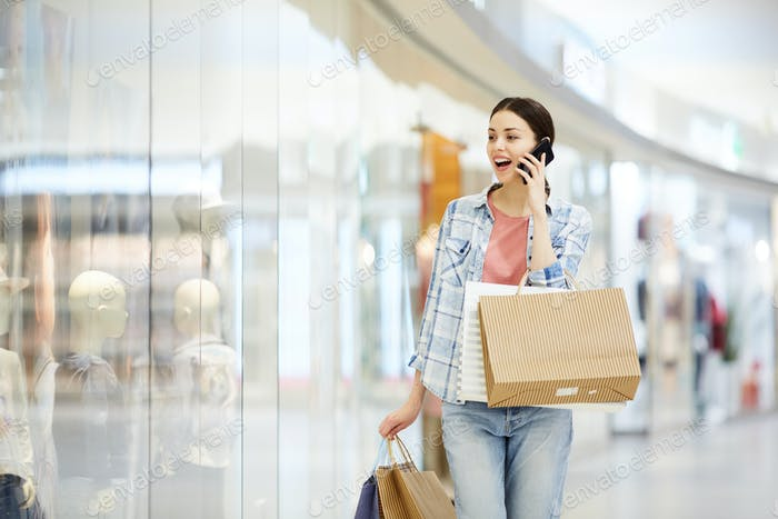 Shocked lady shopaholic talking on phone