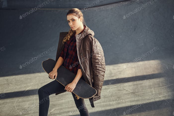 A young girl with a coat covering his shoulders holding on a skateboard