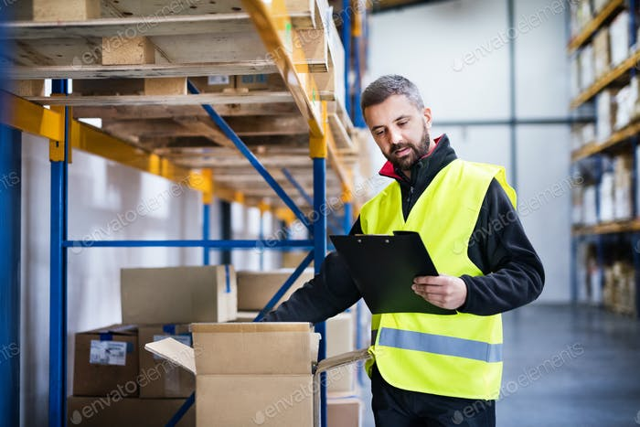 Male warehouse worker with clipboard controlling stock.