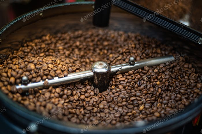 Mixing and roasting brown coffee beans on cooling plate - professional coffee roaster machine during