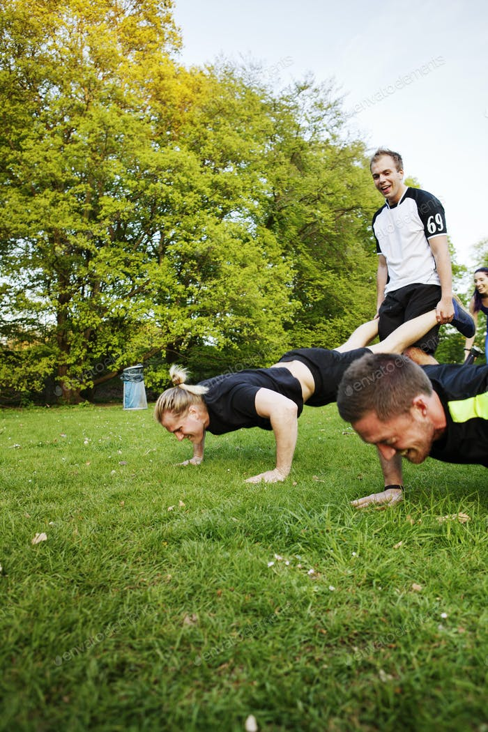 People exercising on grassy field at park