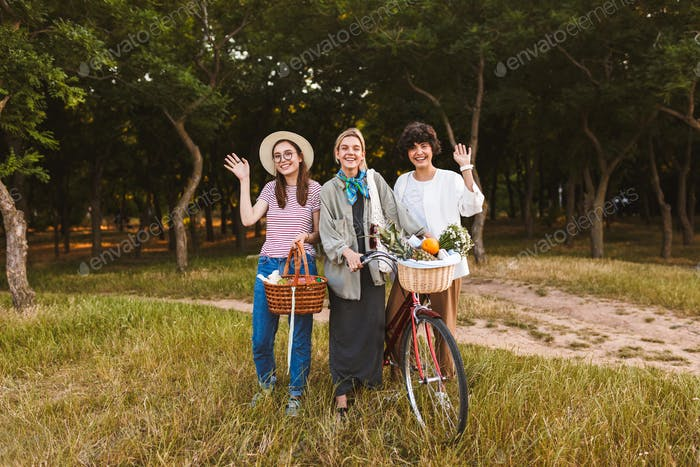 Group of happy girls with bicycle and baskets full of wildflower