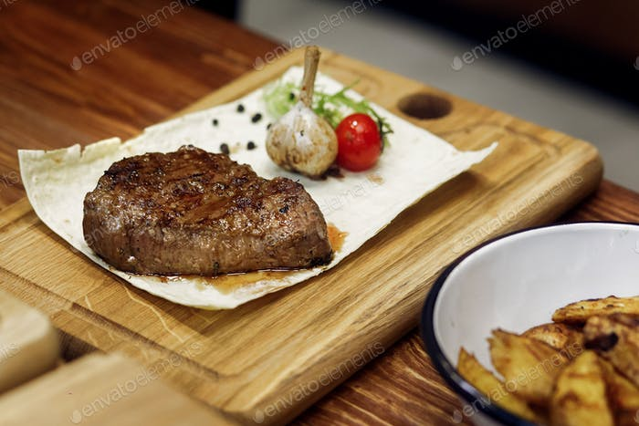 Juicy grilled steak with fried potatos pepper tomato and garlic.