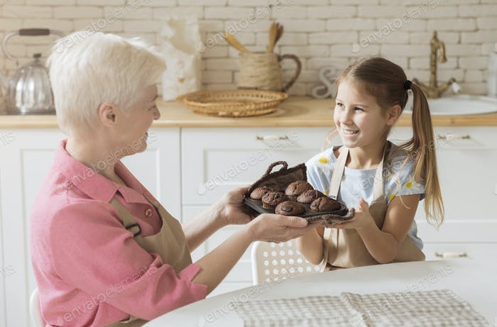 Lächelnd Mädchen und Ihr Oma halten Tablett mit frischen Schokolade Muffins zu Hause