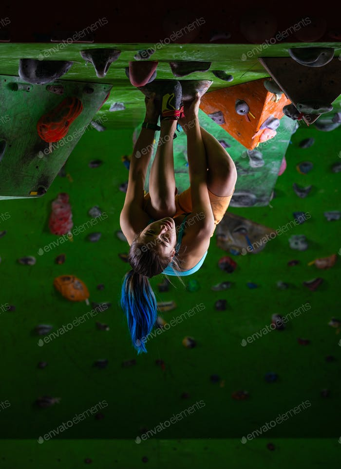 Young woman bouldering in climbing gym