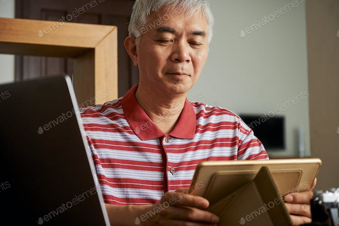Man putting tablet on stand