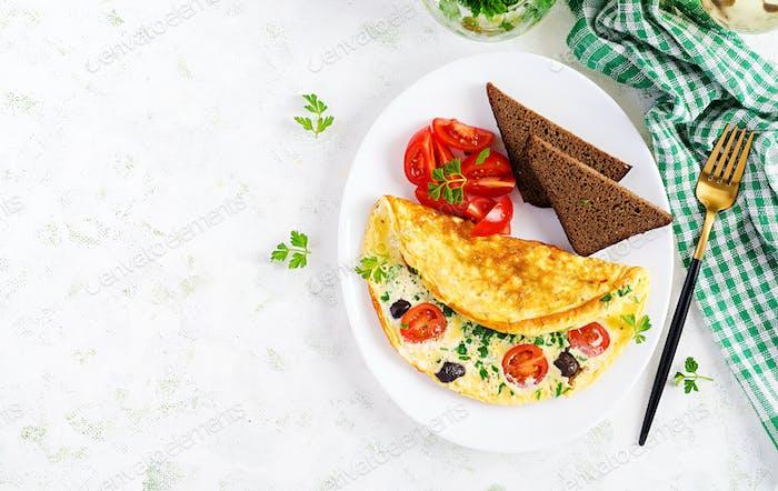 Omelett mit Tomaten, schwarzen Oliven, Hüttenkäse und grünen Kräutern