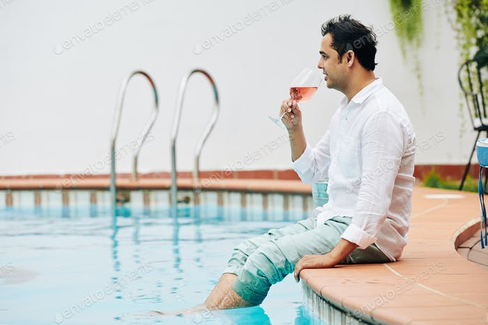 Pensive man resting by pool with wine glass