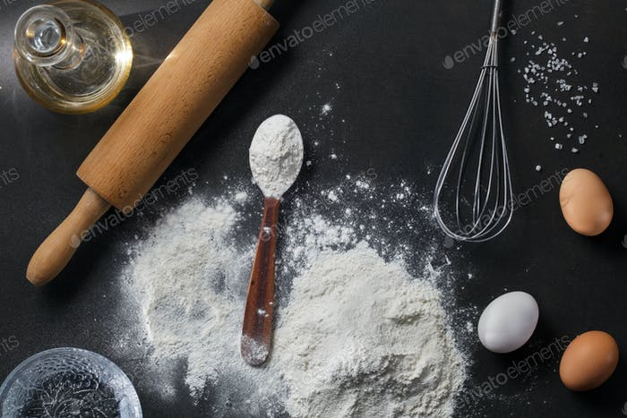 flour and ingredients on black table