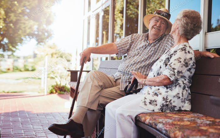 Happy senior couple relaxing on bench outside their house
