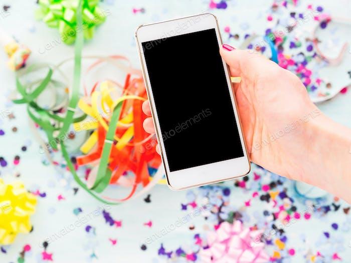 Handy in der Hand über Party-Dekor