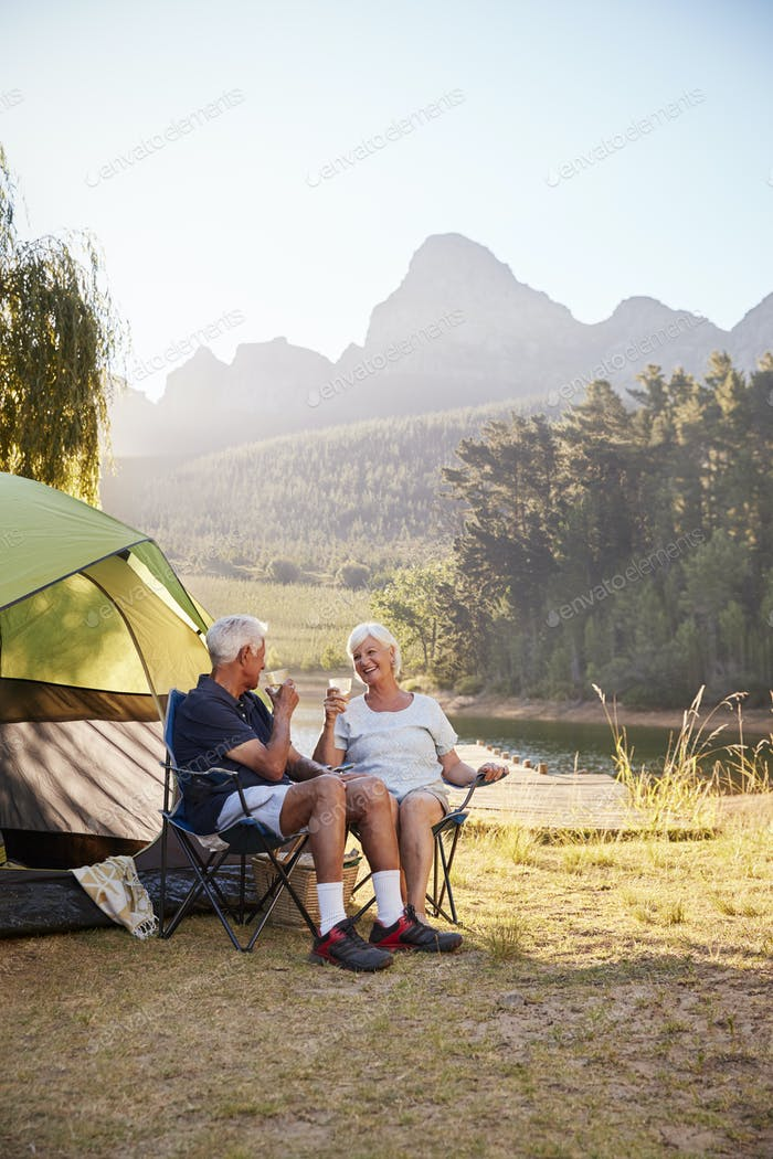 Senior Couple Enjoying Camping Vacation By Lake Making A Toast