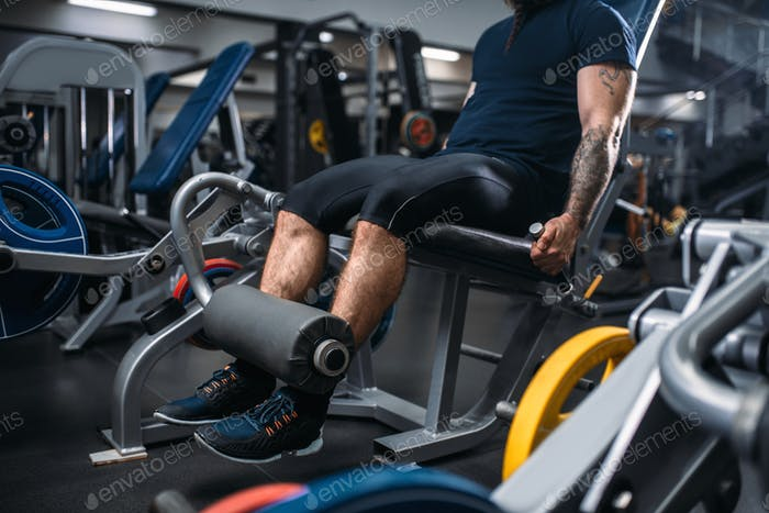 Male person trains legs on exercise machine in gym