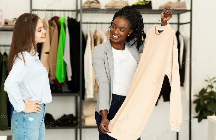 African American Stylist Choosing Clothing For Client In Showroom