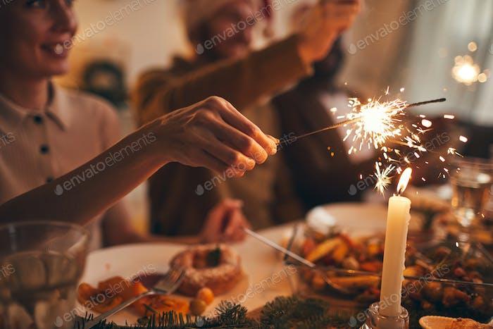 Hand hält Wunderkerze über Tisch