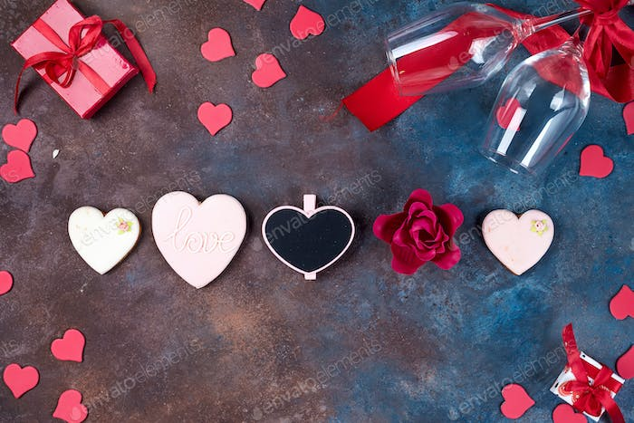 Valentines day background with handmaded hearts, glasses, cookies and gift box on a stone background