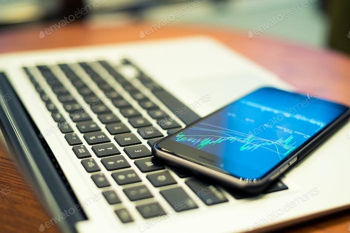 Notebook Computer und Smartphone mit Börsendiagramm