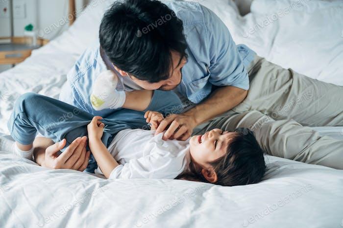 Vater und Tochter spielen zusammen im Schlafzimmer